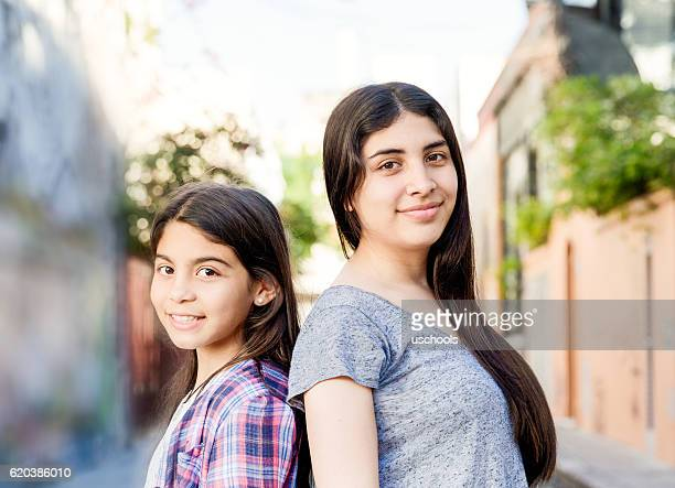 Smiling girls looking at camera on the street
