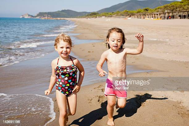 Smiling girls playing in waves on beach