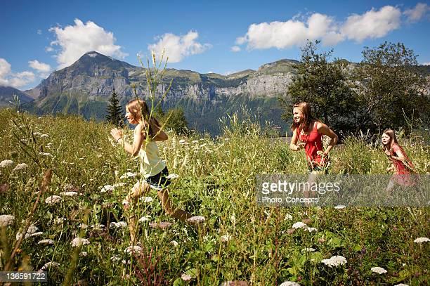 Smiling girls running in tall grass