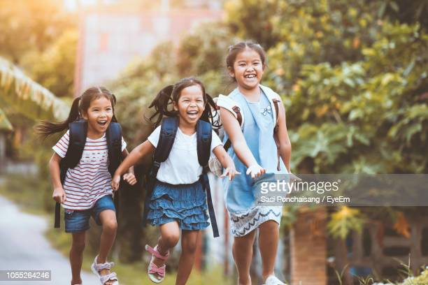 Smiling Girls Running On Road