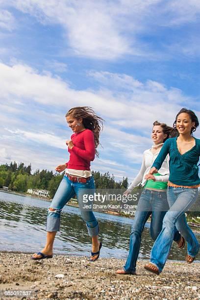 Smiling girls running on rocky beach