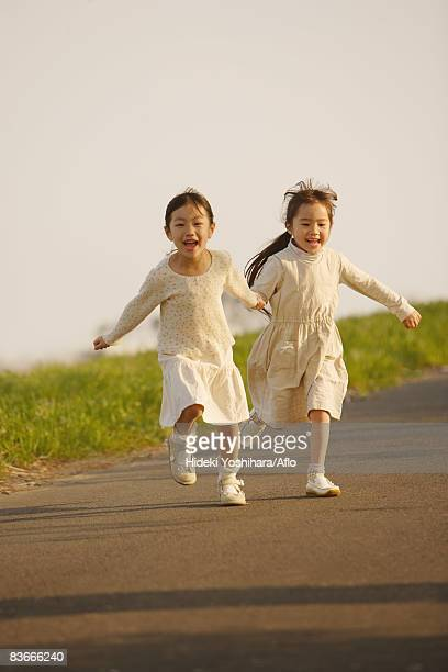 Smiling girls running on the road together