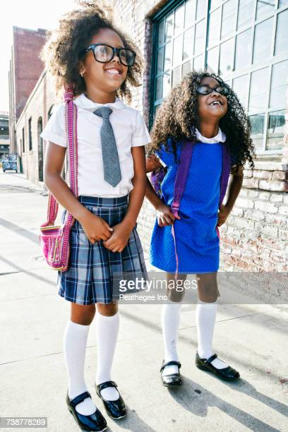 smiling girls standing on sidewalk ready for school - schuluniform stock-fotos und bilder