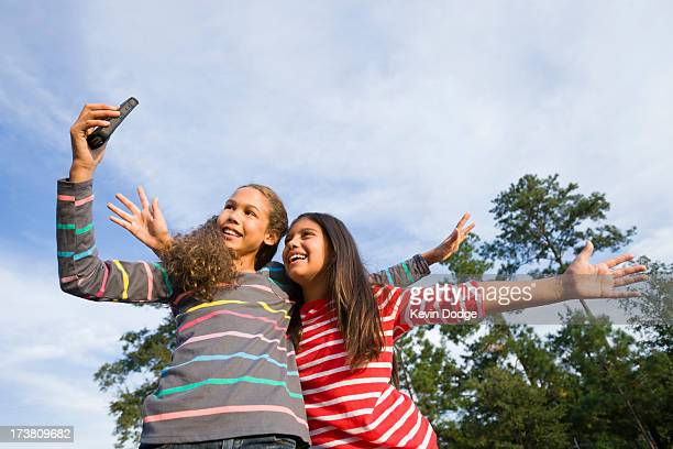 Smiling girls taking pictures outdoors