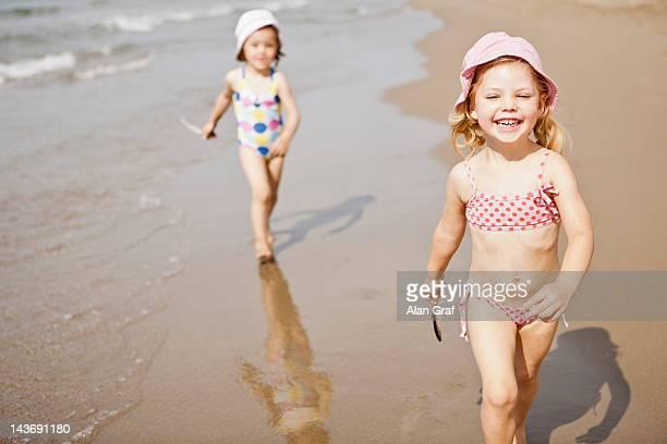 Smiling girls walking in waves on beach