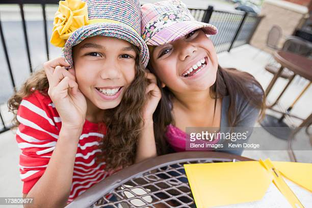 Smiling girls wearing hats at table