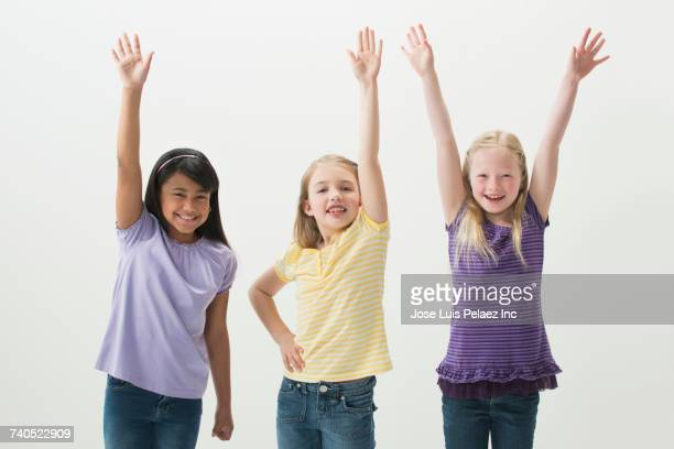 Smiling girls with hands raised