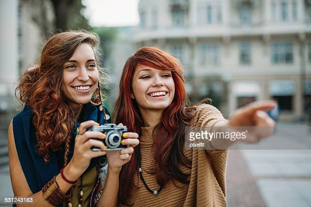 Smiling girls with retro camera outdoors