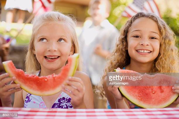 Smiling girls with watermelon wedges