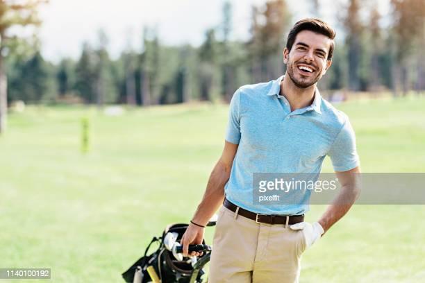 giocatore di golf sorridente che tira una borsa da golf sul campo - mani in tasca foto e immagini stock