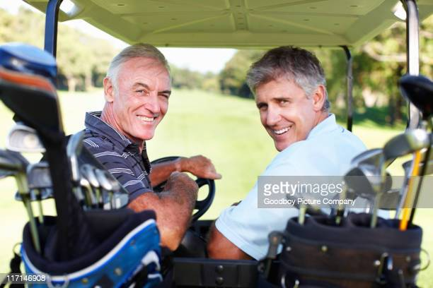 Smiling golfers in a golf buggy