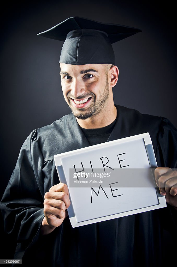 Smiling Graduate With Hire Me Sign : Stock Photo