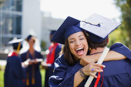 Smiling graduates hugging outdoors - gettyimageskorea