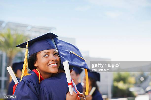 smiling graduates hugging outdoors - high school graduation stock pictures, royalty-free photos & images