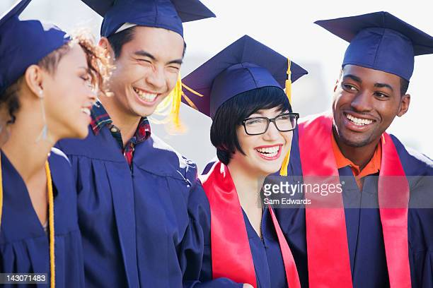smiling graduates standing together - high school graduation stock pictures, royalty-free photos & images