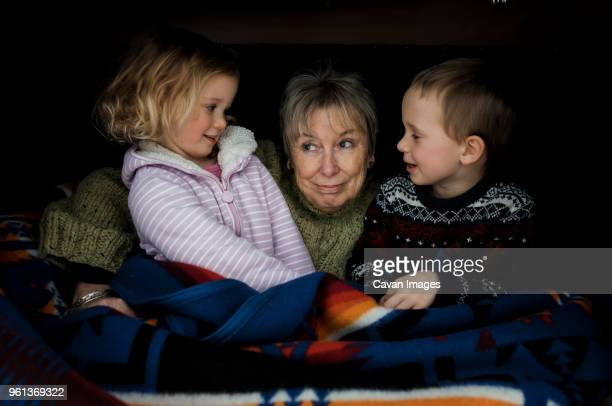 Smiling grandchildren with grandmother sitting in roof tent on car