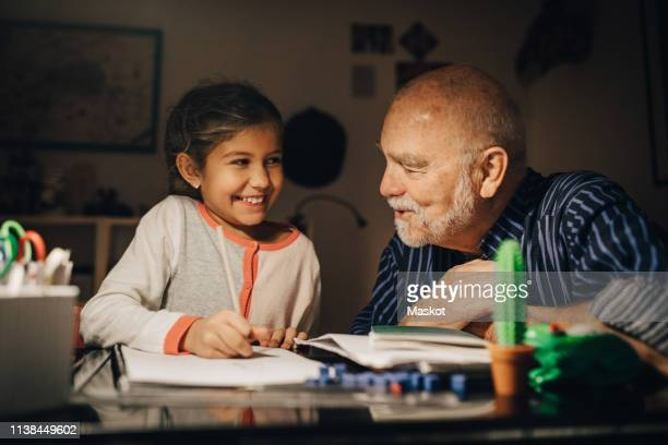 smiling grandfather and granddaughter looking at each other while sitting by desk in house - the_writer's_block stock pictures, royalty-free photos & images
