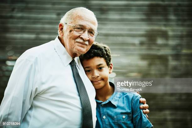 Smiling grandfather and grandson embracing after family dinner party