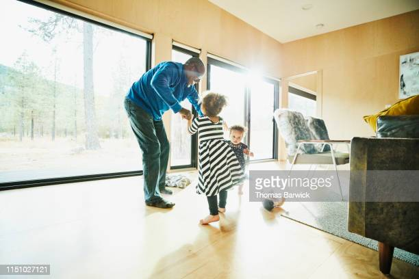 smiling grandfather dancing with two granddaughters in living room - granddaughter stock pictures, royalty-free photos & images