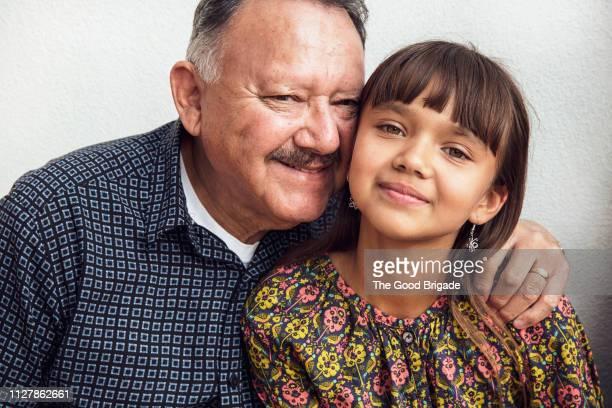 Smiling grandfather embracing granddaughter