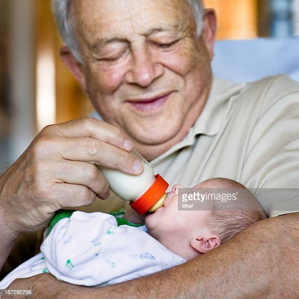 Lächelnd Großvater feeds seinen drei Wochen alten Enkelin
