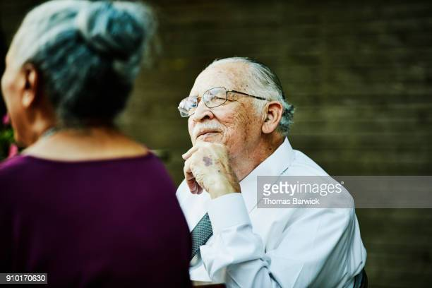 smiling grandfather sitting at head of table during outdoor dinner party - texas independence day stock pictures, royalty-free photos & images