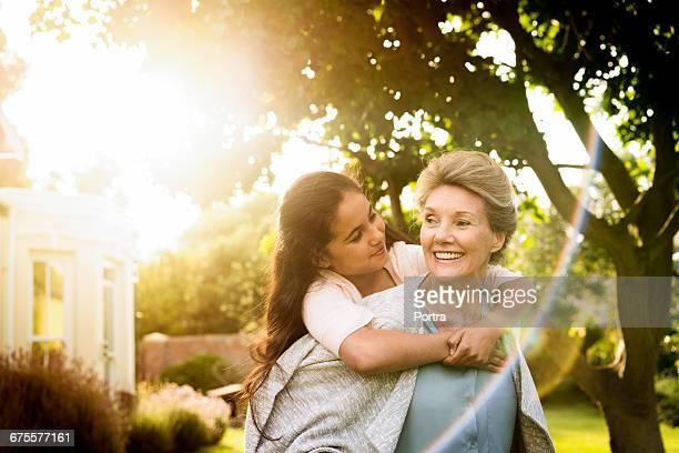 Smiling grandma carrying teenager in yard