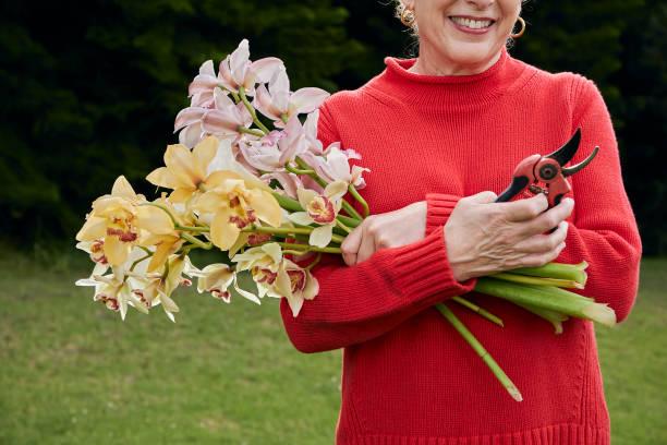 Smiling Grandma Holding Fresh Cut Flowers from the Garden