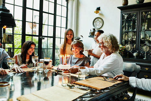 Smiling grandmother admiring birthday cake with candles at dining room table during dinner party with family - gettyimageskorea