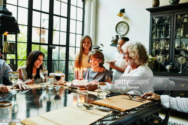 Smiling grandmother admiring birthday cake with candles at dining room table during dinner party with family