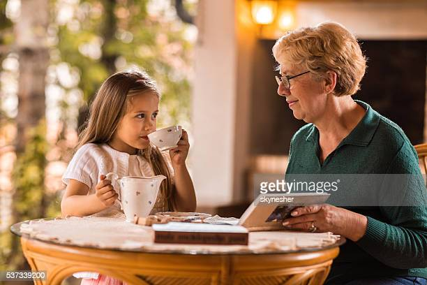 Smiling grandmother and granddaughter enjoying in afternoon tea.