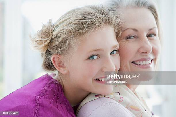 Smiling grandmother and granddaughter hugging