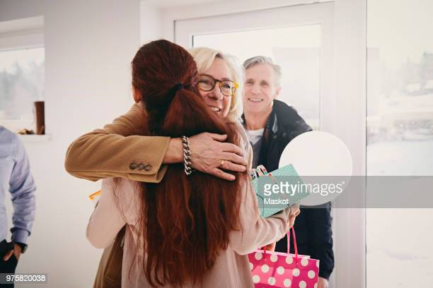 smiling grandmother embracing granddaughter against door at home - arrival stock pictures, royalty-free photos & images
