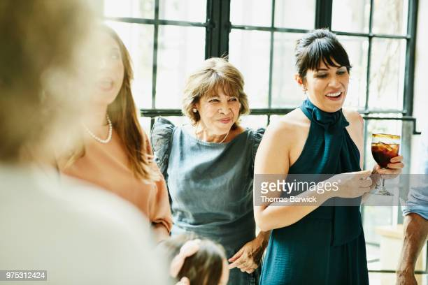 smiling grandmother hanging out with family during dinner party - sleeveless dress stock pictures, royalty-free photos & images