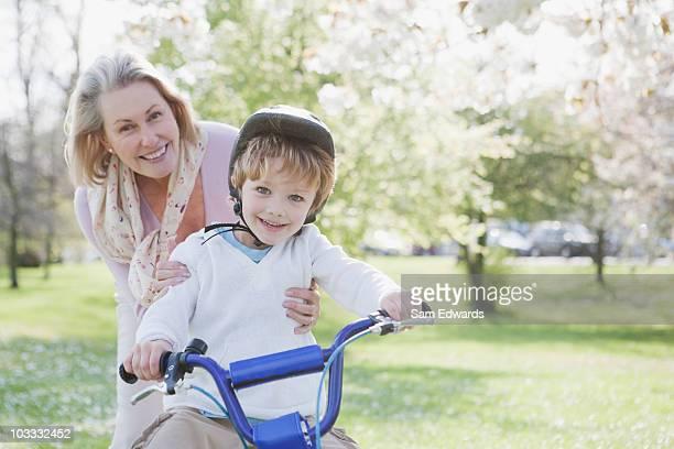 Lächelnd Großmutter umarmen Enkel auf Fahrrad im park