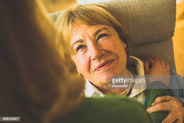 Smiling grandmother looking at adult granddaughter