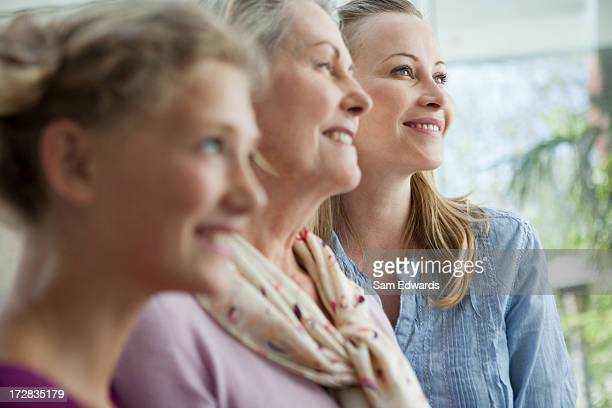 smiling grandmother, mother and daughter looking up - generational family stock photos and pictures
