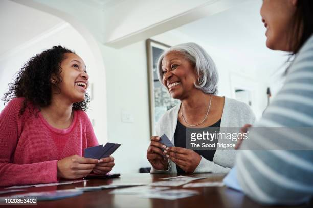 smiling grandmother playing cards with family at home - leisure games stock pictures, royalty-free photos & images
