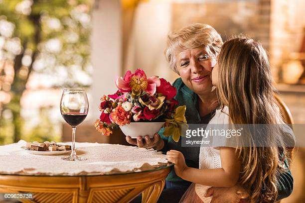 smiling grandmother receiving colorful flowers from her granddaughter. - amado carrillo fuentes fotografías e imágenes de stock