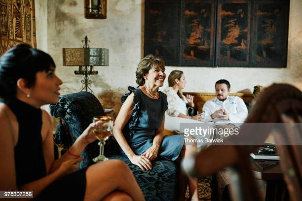 Smiling grandmother sitting in living room with inlaws and children before dinner party