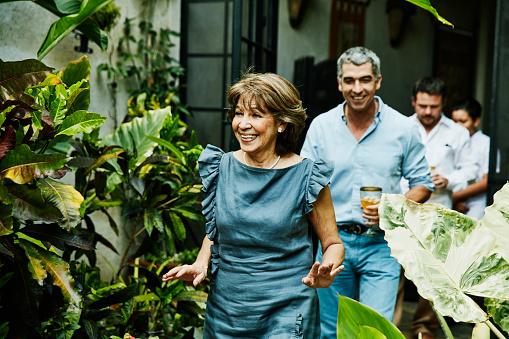 Smiling grandmother walking into backyard during family dinner party - gettyimageskorea