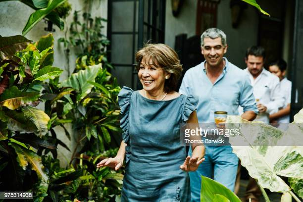 smiling grandmother walking into backyard during family dinner party - part of a series stock pictures, royalty-free photos & images