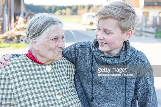 Smiling Grandmother With Grandson In Autumn