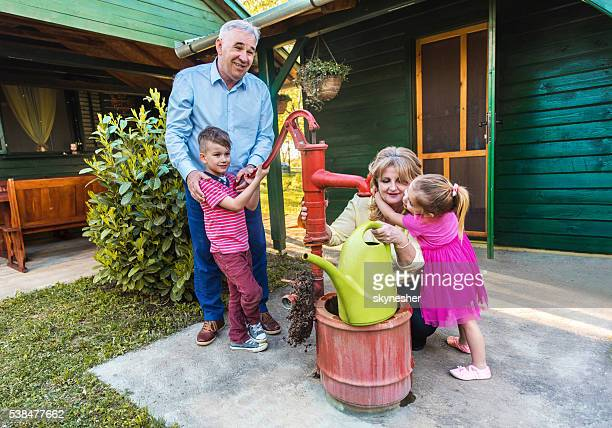 Smiling grandparents enjoying with grandchildren in backyard.