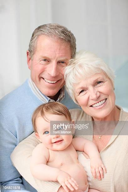 Lächeln Großeltern hält baby