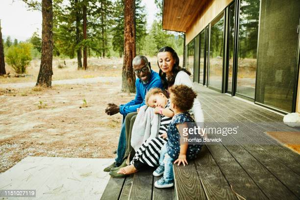 Smiling grandparents sitting with young granddaughters of porch of cabin
