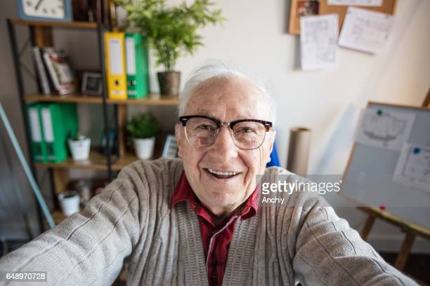 Smiling gray haired senior adult taking photo of himself