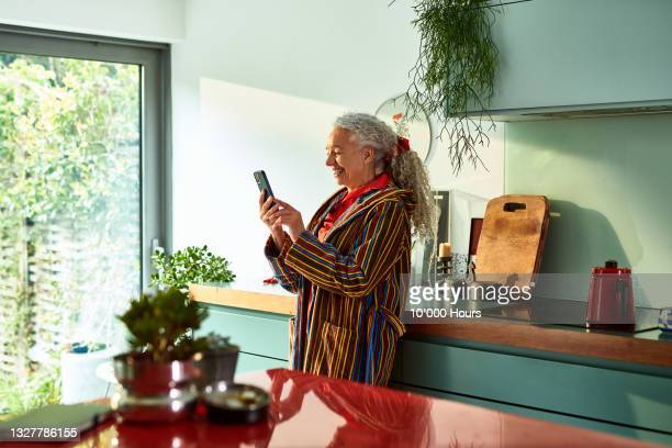 smiling grey haired woman speaking on video call - greater london stock pictures, royalty-free photos & images