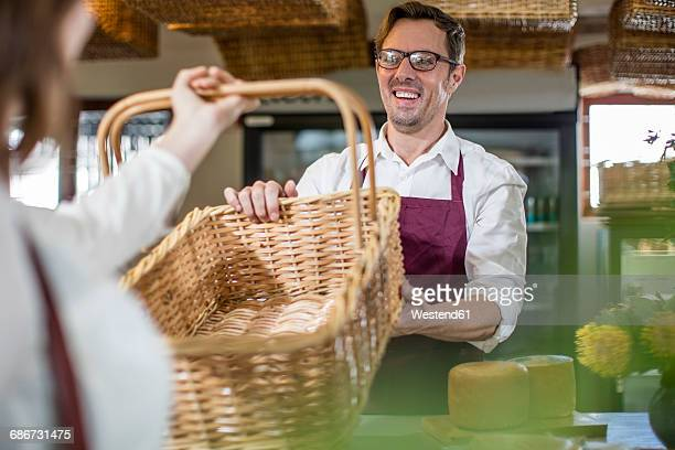 Smiling grocer serving customer in a farm shop