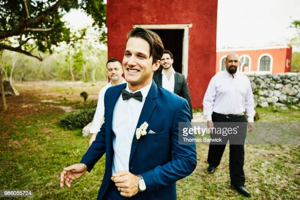 smiling groom walking with wedding party to reception after ceremony at tropical resort - wedding after party stock pictures, royalty-free photos & images